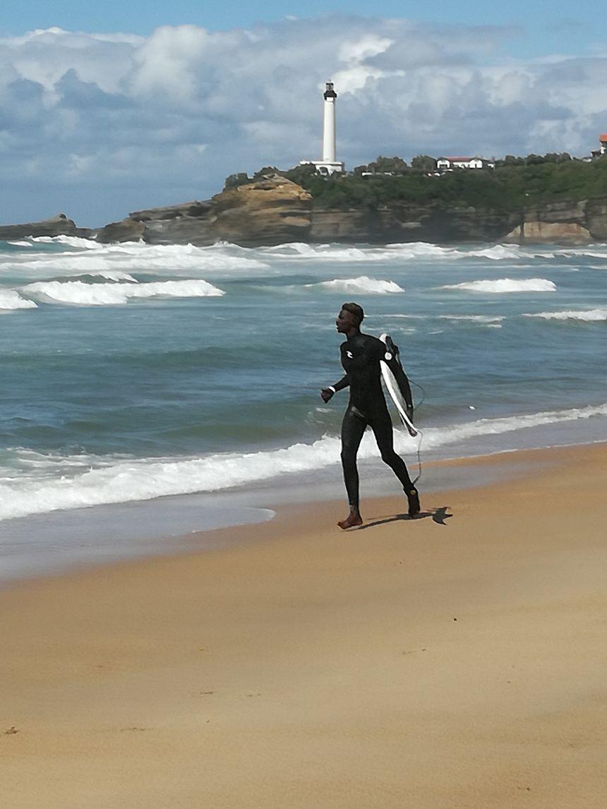 Un surfeur sénégalais partant s'entrainer sur la Grande Plage. Une image encore rare y compris au Sénégal - Radio France
