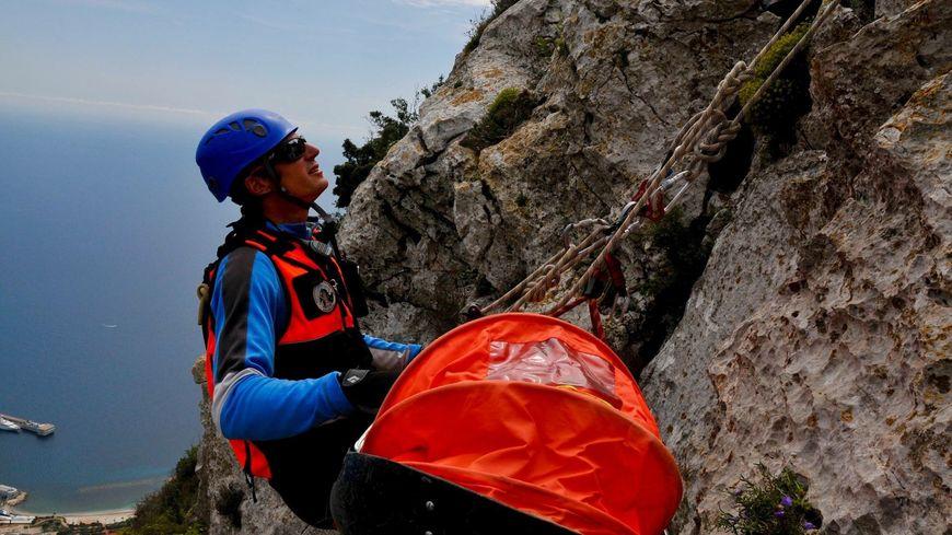 Un secouriste du PGHM des Alpes-Maritimes remonte avec une civière à l'aide d'un treuil
